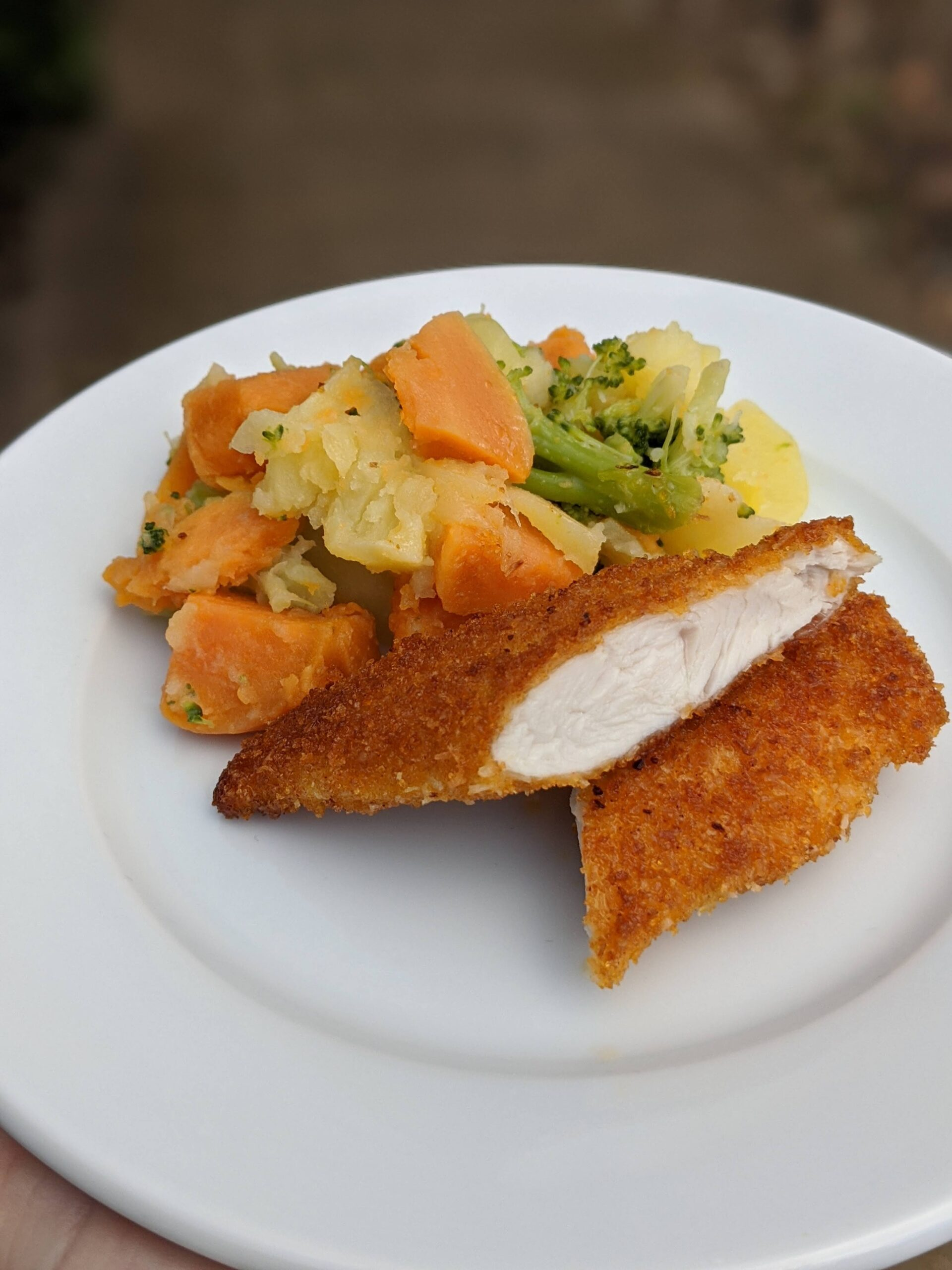 Coconut crusted chicken schnitzel served with vegetable mash